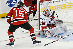 Apr 15, 2009; Newark, NJ, USA; Carolina Hurricanes goalie Cam Ward (30) makes a mask save on a shot by New Jersey Devils right wing Jamie Langenbrunner (15) during the third period of game one of the eastern conference quarterfinals of the 2009 Stanley Cup playoffs at the Prudential Center. The Devils defeated the Hurricanes 4-1 to take a 1-0 series lead.