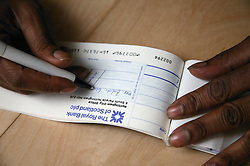 Close up of Single parent writing out a cheque from his cheque book,