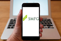 Using iPhone smartphone to display logo of SMFG, Sumitomo Mitsui Financial Group, Inc., a Japanese financial services company.