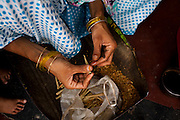 Nafeesa, 27, rolls bidis (indian cigarettes) in her house in a slum in Tonk, Rajasthan, India, on 19th June 2012. Nafeesa's health deteriorated from bad birth spacing and over-working. While her husband works far from home, she rolls bidis to make an income and support the family. She single-handedly runs the household and this has taken a toll on her health and financial insufficiencies has affected her children's health. Photo by Suzanne Lee for Save The Children UK