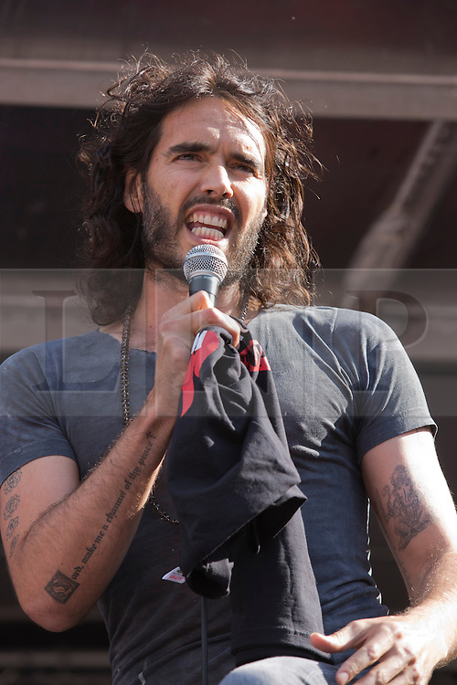 "© Licensed to London News Pictures. 21/06/2014. London, England. Actor, comedian and political campaigner Russell Brand speaks at the No More Austerity demonstration and festival in Parliament Square, London. The event was organised by the People's Assembly. He stripped and put on a shirt with the Spanish firefighters' slogan ""We rescue people, not banks!"" Photo credit: Bettina Strenske/LNP"