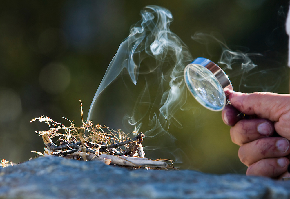 Lighting a fire with a magnifying glass