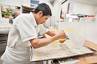 Side view of a young male baker making pastry in bakery
