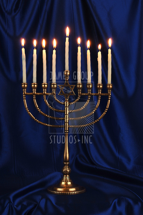 Gold menorah with lit candles on royal blue background