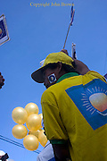 Balloons float in the sky while a man is attending an election campaign rally for the opposing CNRP led by Sam Rainsy in Kampong Cham, Cambodia.