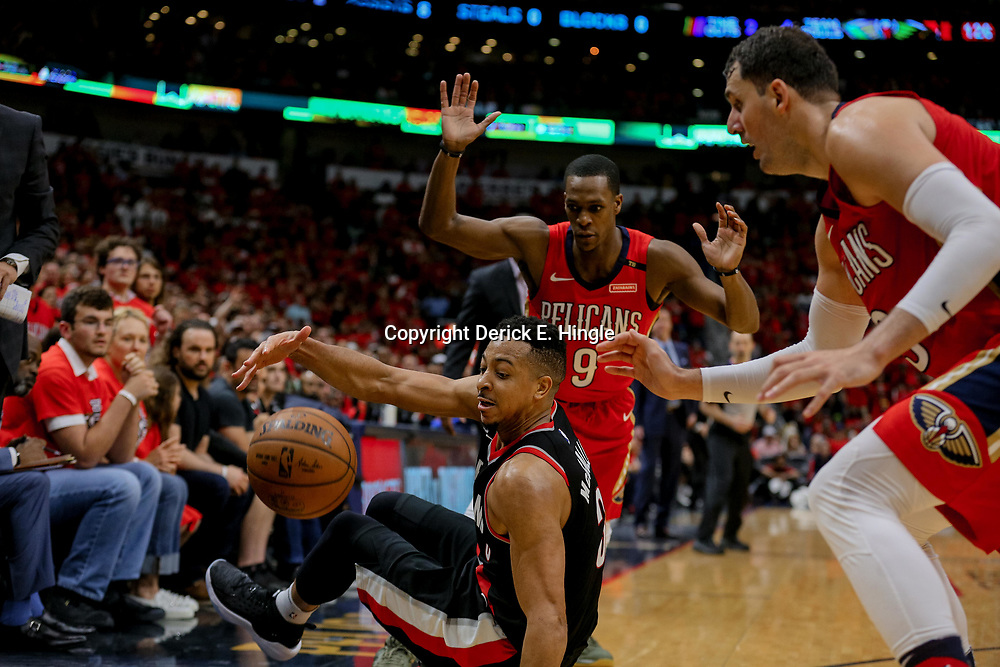 Apr 21, 2018; New Orleans, LA, USA; Portland Trail Blazers guard CJ McCollum (3) is forced out of bounds by New Orleans Pelicans guard Rajon Rondo (9) and forward Nikola Mirotic (3) during the fourth quarter in game four of the first round of the 2018 NBA Playoffs at the Smoothie King Center.  Pelicans defeated the Trail Blazers 131-123 sweeping the series and advancing to the western conference semi-finals.  Mandatory Credit: Derick E. Hingle-USA TODAY Sports