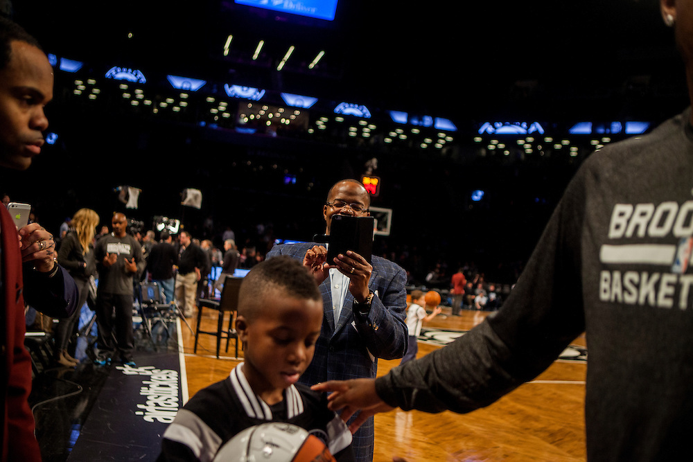 BROOKLYN, NY - MARCH 2, 2015:   Brooklyn District Attorney Kenneth P. Thompson takes a photo of his son Kenny as he meets players from the Brooklyn Nets before a game between the Nets and the Golden State Warriors at the Barclay's Center.