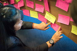 """21 July 2018, Amsterdam, the Netherlands: Participants stick words that capture hopes and challenges for a coordinated response to HIV onto a symbolic bridge, built as an expression of their commitment to working together for a world without AIDS as a public health threat. Taking place at the Planetarium Gaasperplas in Amsterdam, the Netherlands on 21-22 July 2018, the World Council of Churches - Ecumenical Advocacy Alliance in collaboration with many faith and other partners organizes its bi-annual International Interfaith Event on HIV. Under the theme """"Faith Building Bridges"""", the event is affiliated to the 2018 International AIDS Conference, AIDS 2018, held in Amsterdam on 23-27 July 2018."""