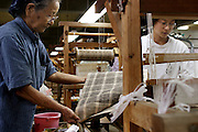 Many Okinawans used to work into their nineties, farming, and weaving bashofu, a fine fabric made from a local banana fiber. Bashofu weaving was a home-based craft, and highly valued, but there are few, if any, weavers producing the fabric at home anymore. The workshop of Toshiko Taira, 87, at left, with a young apprentice, in the northern Okinawa village of Kijoka, is virtually all that is left of the art. She has been designated a national treasure of Japan. She and her daughter are attempting to keep the fine practice alive. (Supporting image from the project Hungry Planet: What the World Eats)