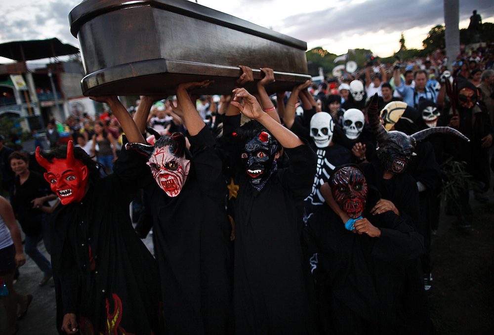 """People dress of the nicaraguan traditional characters load a coffin during a simulated burial of the """"Sadness and poverty of the soul' during celebration of the International Poetry Festival in Granada, Nicaragua, Wednesday, Feb 16, 2011."""