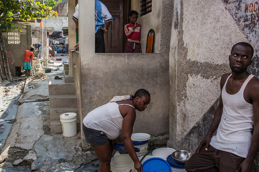 Residents of Bizoton, a neighborhood in the Carrefour area, gather water from a faucet as dirty water flows in front of their houses on Friday, December 19, 2014 in Port-au-Prince, Haiti. Due to a new highway, heavy rain causes contaminated water to flow into homes, which recently resulted in a cholera outbreak that sickened more than 300 people. Still, nothing has been done to keep the homes from flooding.