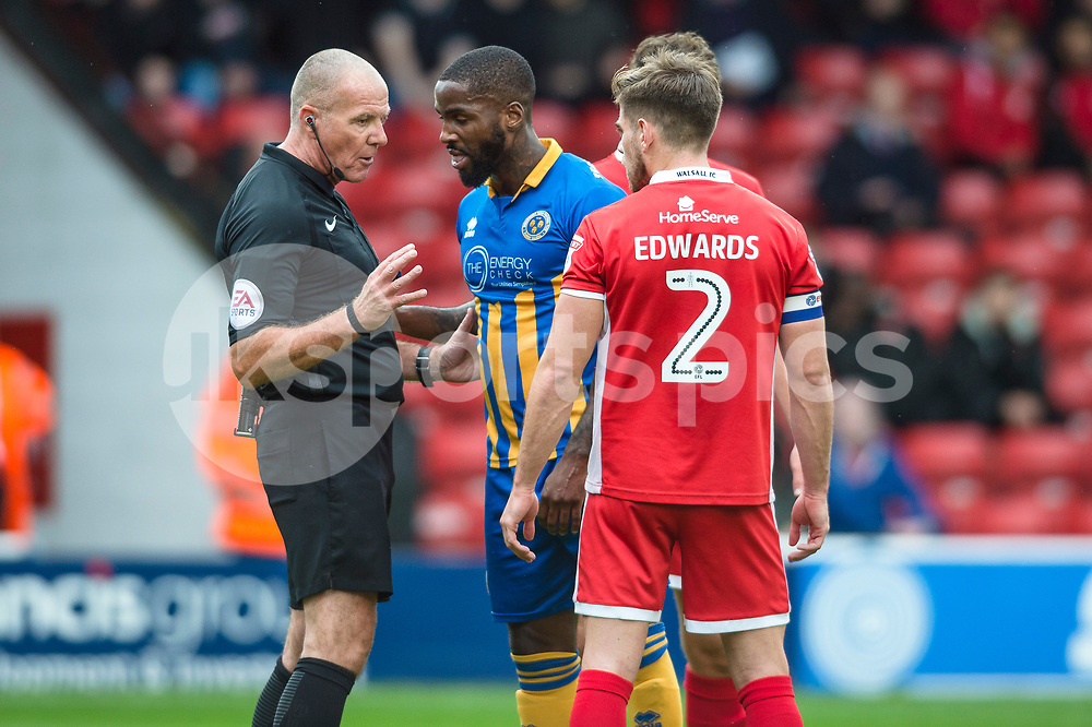 Match Referee Graham Salisbury speaks to the two captains after being surrounded by players as he awards a penalty to Shrewsbury during the EFL Sky Bet League 1 match between Walsall and Shrewsbury Town at the Banks's Stadium, Walsall, England on 7 October 2017. Photo by Darren Musgrove.