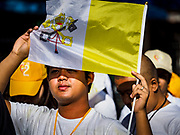 30 NOVEMBER 2017 - YANGON, MYANMAR: A man uses a Vatican flag as a sun shield during the Papal Mass at St. Mary's Cathedral in Yangon. Thursday's mass was his last public appearance in Myanmar. From Myanmar the Pope went on to neighboring Bangladesh.    PHOTO BY JACK KURTZ