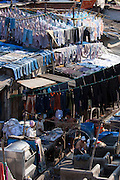 Indian hand laundry, Dhobi Ghat, and laundryman using traditional flogging stone to wash clothing at Mahalaxmi, Mumbai, India