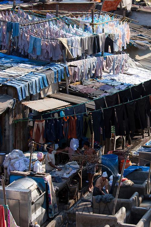 Indian hand laundry, Dhobi Ghat, and laundryman using traditional flogging stone to wash clothing at Mahalaxmi, Mumbai, India