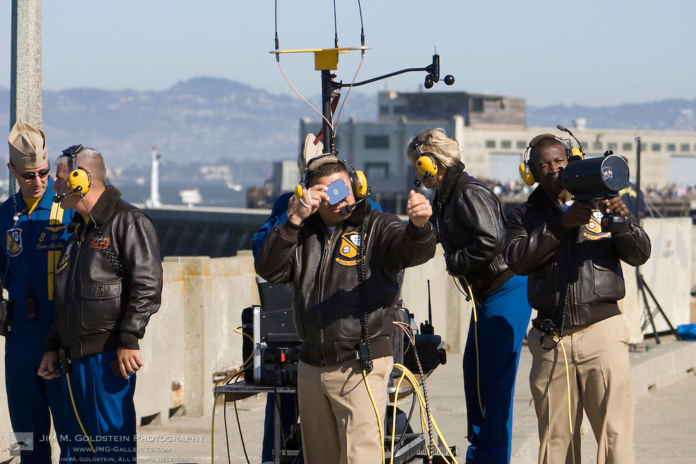 Blue Angels support crew reflect sunlight and shine an electronic beacon at Blue Angels jets in flight to assist them in navigating the Fleet Week performance in San Francisco