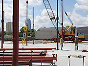 Construction workers at Grady Middle School direct the installation of vertical beams for the school's new classroom wing on Monday, May 4, 2015.