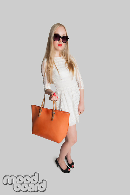 Portrait of fashionable girl carrying purse over gray background
