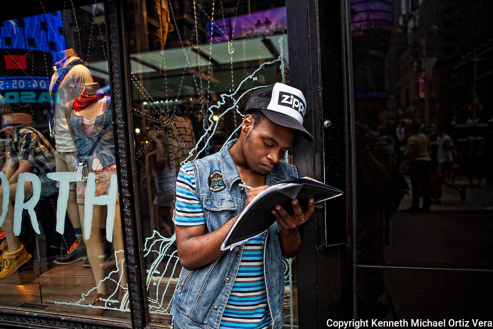 A Young Teen is filling out a job application outside of the Hardrock Cafe in Time Square, New York City.
