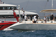 Guests relax aboard luxury yachts as they line up along edge of race course to watch America's Cup fleet racing; Valencia, Spain.