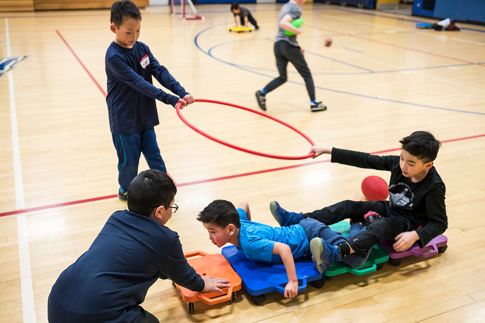 Max Pfliger, left, and the Wahe boys play during a lunar new year event hosted by Families Through Korean Adoption (FTKA) in the gym and school cafeteria of St. Dennis Church in Madison, Wis., on Feb. 10, 2018. The event celebrated the passing of the lunar new year, and is one of several events for FTKA-member families and children to gather and enjoy cultural fun, food and play. (Photo by Jeff Miller - www.jeffmillerphotography.com)