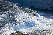 Gushing glacial river water at falls of Gullfoss Waterfall in glacial landscape of South Iceland