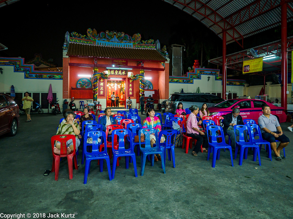 """12 JANUARY 2018 - BANGKOK, THAILAND: Spectators at a Chinese opera performance at the Chaomae Thapthim Shrine in the Dusit district of Bangkok. Many Chinese shrines and temples host Chinese operas during the Lunar New Year. Lunar New Year is 16 February this year and opera troupes are starting their holiday engagements at local Chinese temples and shrines. The new year will be the """"Year of the Dog."""" Chinese New Year, also called Lunar New Year or Tet, is widely celebrated in Chinese communities around the world. Thailand has a large Chinese community and Lunar New Year is an important holiday.      PHOTO BY JACK KURTZ"""