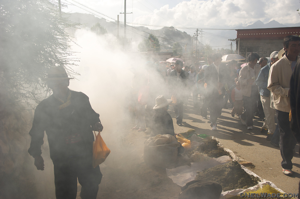 People walk through sweet smelling juniper smoke at a festival at Ganden Monastery in Lhasa, Tibet.