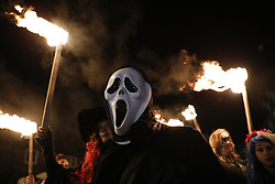 © Licensed to London News Pictures. 05/11/2016. Edenbridge, UK. People carry torches as they take part in the Edenbridge bonfire procession before an effigy of US Presidential candidate Donald Trump burns at the annual Edenbridge traditional fireworks night celebrations. The 36 ft tall figure is holding the head of his Democrat rival Hillary Clinton. Photo credit: Peter Macdiarmid/LNP