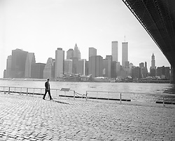 man walking on the Brooklyn side of New York Skyline overlooking The Twin Towers in New York City