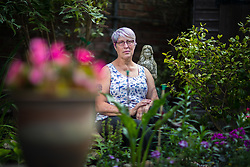 © Licensed to London News Pictures . 13/08/2017 . Salford , UK . Joy Watson (59) pictured in her garden in Eccles . Joy has Alzheimer's disease and has had to quit her job as a carer . As a campaigner and educator on the needs of people with dementia , she was praised by former Prime Minister David Cameron , who awarded her a Points of Light Award . But she and her retired husband and full-time carer, Tony, say they now struggle to pay their bills after an assessment by the DWP saw all their financial support withdrawn . For more information see http://www.mirror.co.uk/news/uk-news/woman-dementia-praised-david-cameron-10983661 . Photo credit : Joel Goodman/LNP