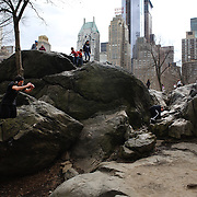 Youngsters play on rock formations in Central Park, Manhattan, New York, USA. 26th March 2013. Photo Tim Clayton