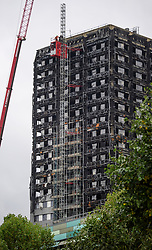 © Licensed to London News Pictures. 13/10/2017. London, UK.  Workmen erect a scaffolding structure around Grenfell Tower in Notting Hill, as work begins to install a cover around the the buildings external walls. Over 80 people are thought to have perished in a devastating fire that ripped through the 24 storey residential building in the early hours of June 14, 2017.Photo credit: Ben Cawthra/LNP