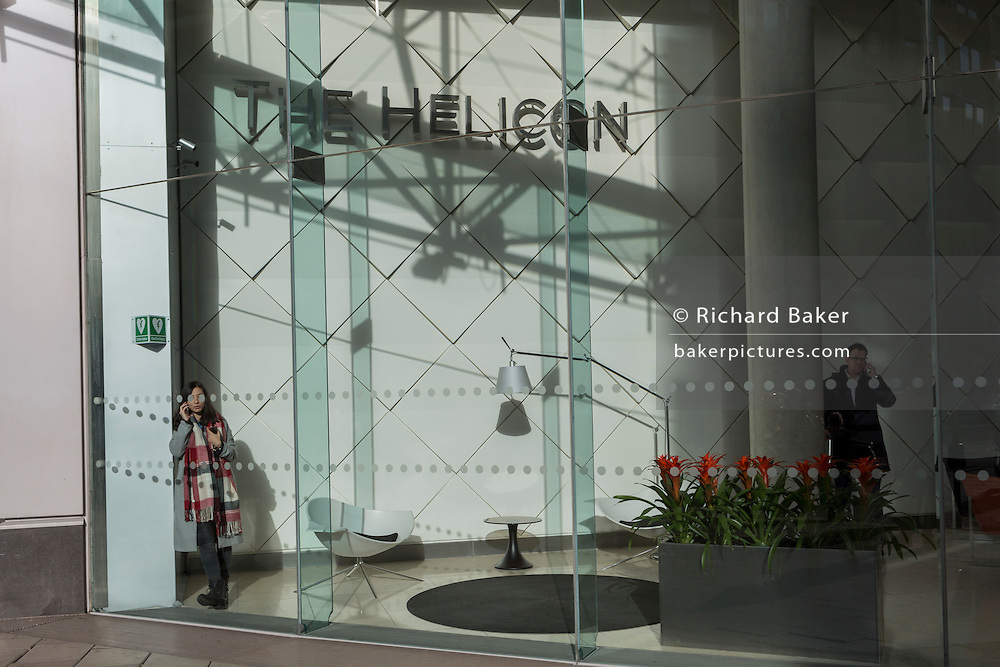 A young woman holds a conversation on her phone while standing in the foyer of The Helicon, a company office space, on 16th February 2017, on Moorgate, in the City of London, England.