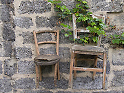 two weathered wooden chairs hanging on a wall
