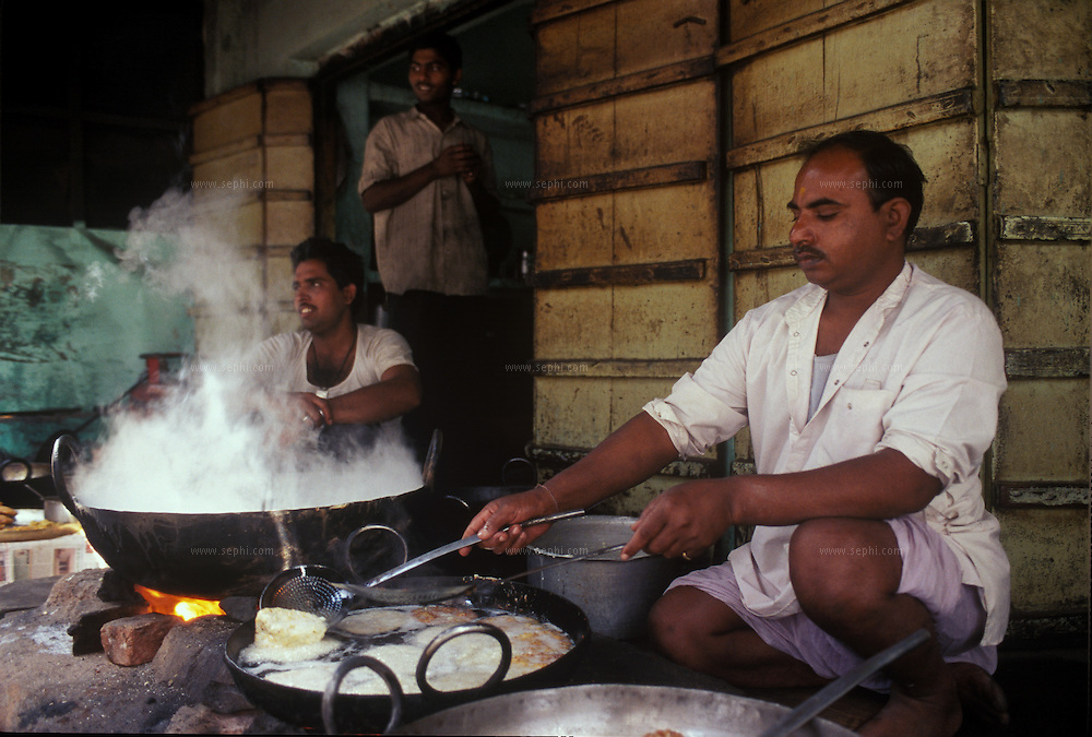 A street vendor in Pushkar cooking malpua. Malpua is then dipped into a syrup of water, sugar and sweet lime. It is a sweet delicacy made of Condensed milk, Semolina, Plain flour and jaggery (gur). Rajasthan, India