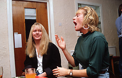 Two women with hearing impairments sitting at table in bar using sign language to communicate,
