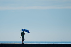 ©Licenced to London News Pictures. Aberystwyth,UK. 22/07/2018. UK. A man with an umbrella to shield him from the sun,  walking along the harbour in the heat haze Aberystwyth on a gloriously hot and sunny Sunday in west wales. The UK wide heatwave continues, with no respite from the very dry weather and temperatures are expected to exceed 30ºc again by the end of the week. Photo credit: Keith Morris/LNP