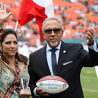 Gloria and Emilio Estefan are awarded a trophy for community help prior to an NFL football game between the New York Jets and the Miami Dolphins on Sunday, September 23, 2012 at SunLife Stadium in Miami, Florida. (AP Photo/Alex Menendez)