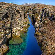"Peningagjá (""coin fissure"") is the popular name for this fissure in Þingvellir (Thingvellir) National Park, Iceland. It is formally known as Nikulásargjá. The boundary where tectonic plates of North America (left) and Eurasia (right) run through Iceland and are slowly drifting apart (about 2cm a year)."