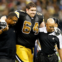 September 25, 2011; New Orleans, LA, USA; New Orleans Saints offensive tackle Zach Strief (64) is helped off the field by trainers during the third quarter against the Houston Texans at the Louisiana Superdome. The Saints defeated the Texans 40-33. Mandatory Credit: Derick E. Hingle