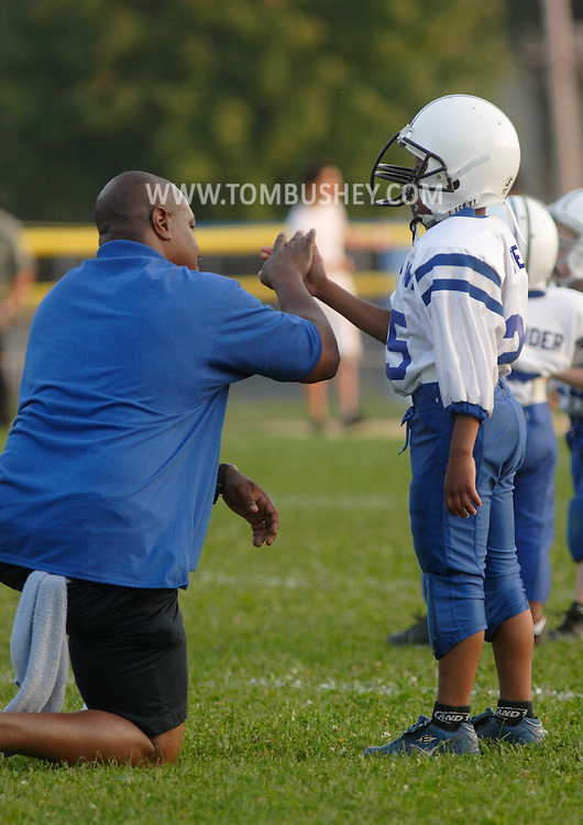 Middletown, NY - A Middletown coach kneels to talk to a player during an Orange County Youth Football League game against Goshen at Watts Park in Middletown on Sept. 22, 2007.