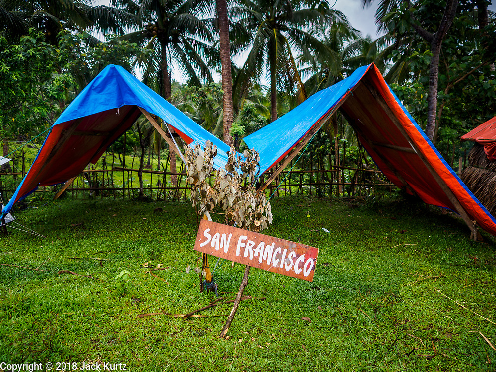 26 JANUARY 2018 - SANTO DOMINGO, ALBAY, PHILIPPINES: A temporary shelter in a field near Santo Domingo for people evacuated from the Mayon volcano. Mayon Volcano was relatively quiet Friday, but the number of evacuees swelled to nearly 80,000 as people left the side of  the volcano in search of safety. There are nearly 12,000 evacuees in Santo Domingo, one of the most impacted communities on the volcano. The number of evacuees is impacting the availability of shelter space. Many people in Santo Domingo, on the north side of the volcano, are sleeping in huts made from bamboo and plastic sheeting. The Philippines is now preparing to house the volcano evacuees for up to three months.        PHOTO BY JACK KURTZ