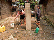 Mar. 16, 2009 -- LUANG PRABANG, LAOS: A family does their laundry at a well built by World Vision Singapore in a village on Highway 13 south of Luang Prabang, Laos. Highway 13 is the main highway in Laos and carries tourist and truck traffic between the capital Vientiane and Luang Prabang. Laos is one of the poorest countries in the world and many NGOs are very active there. Photo by Jack Kurtz