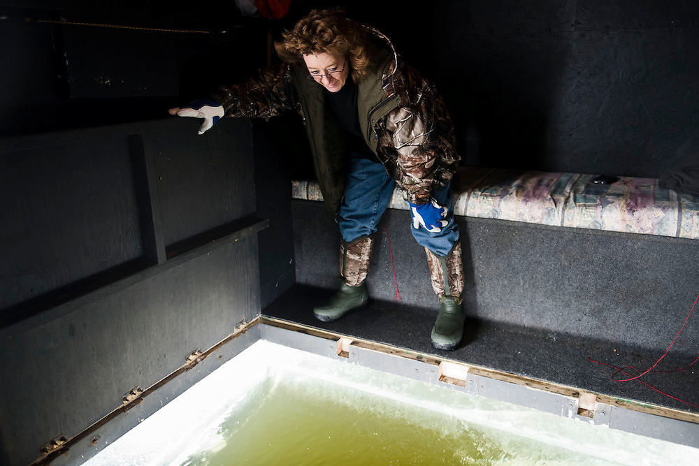 PIPE, WI -FEB. 16, 2015: Connie Petska, 46, waits in her shanty to have it lowered over the hole that was drilled to fit the size of their shanty's opening Monday, Feb. 16, 2015. 13,000 licenses were sold for the 2015 sturgeon spearing season, and 233 fish were caught Monday between all of the registration stations, with 62 being registered in Stockbridge. The season started Feb. 14, 2015 and lasted until Feb. 21, 2015 on Lake Winnebago with a total of 1870 sturgeon speared. The average success rate for spearers is 10-12% and some people go years without spotting anything from their shanty. Lauren Justice for The New York Times