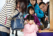 Four-year-old Mao Konishi and her mother Kae say a prayer during a remembrance service to mark the one year anniversary of last year's magnitude 9 earthquake and tsunamis in Ofunato City, Iwate Prefecture, Japan on 11 Mar. 2012. .Photographer: Robert Gilhooly