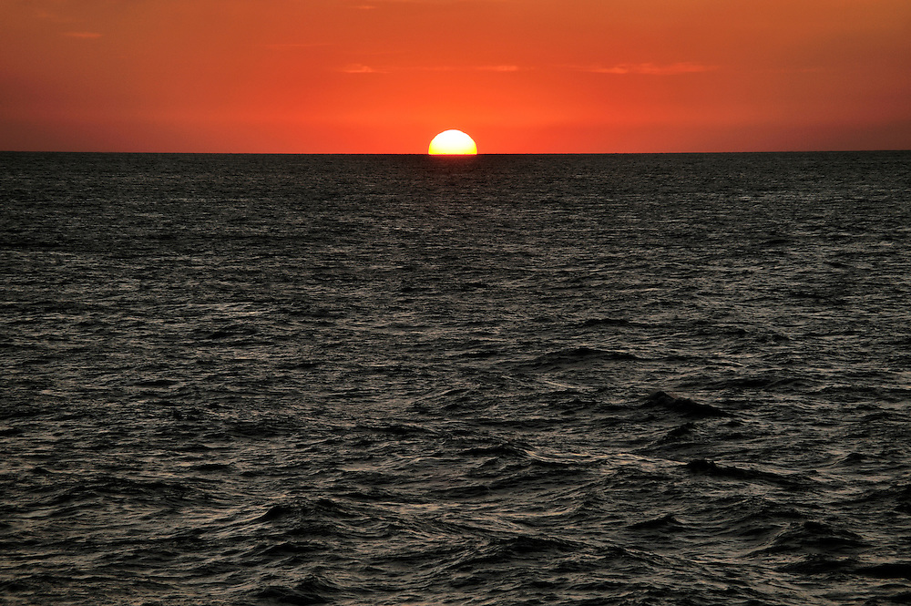 Sunset sunrise over ocean sea rising setting sun red