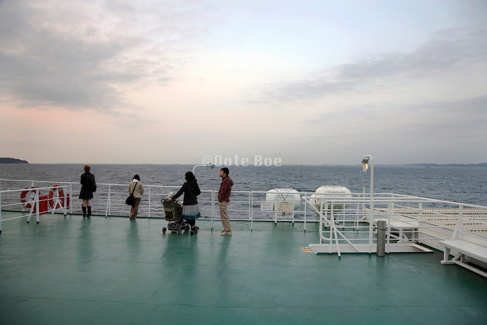 passengers on a ship looking out over the water