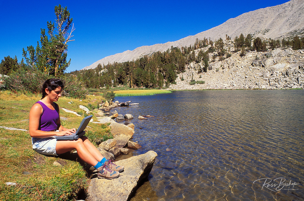 Woman using a laptop computer on the shore of Heart Lake, John Muir Wilderness, Inyo National Forest, Sierra Nevada Mountains, California