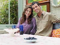 Young couple sitting at verandah table smiling portrait